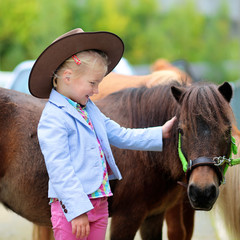 Lovely cowgirl caressing little pony horse in the farm. Pretty preschooler girl wearing cowboy hat...