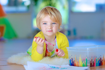 Happy little child, adorable blonde toddler girl lying comfortable on tiles floor on warm lambskin drawing on paper with colorful pens on sunny day