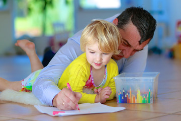 Father and child having quality time together at home. Happy family of two, loving caring dad with  adorable toddler girl, lying cozy on tiles floor on warm lambskin drawing with colorful pencils
