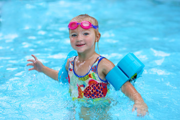 Little child enjoying swimming pool. Cute toddler girl wearing colorful swimsuit, pink goggles and blue armbands having fun in the water. Adorable sportsman kid promoting healthy lifestyle.