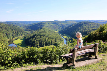 Little child sitting at the bench enjoying elevated view from panoramic viewpoint of beautiful Giant's tomb lying inside the bend of the river Semois located nearby the city of Bouillon, Belgium.