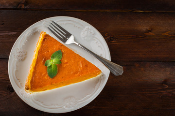 A piece of pumpkin pie with mint, white plate, fork on dark wooden background, copyspace
