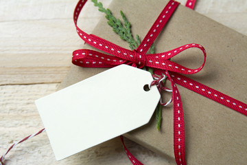 Gift box, wrapped in recycled paper, red bow and tag on wood bac