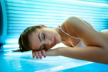 young woman laying on solarium bed