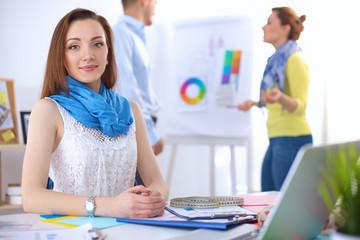 Portrait of attractive female  designer sitting on desk  in