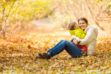 Happy woman and her little son having fun in an autumn park. The boy kissing mother while sitting on her lap.
