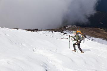 Fototapete - Backpacker woman hiking ascending walking snow mountain.