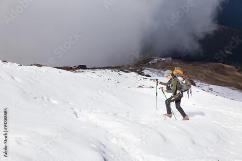 Wall mural Backpacker woman hiking ascending walking snow mountain.