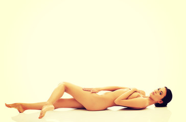 Nude woman on the floor covering intimate places