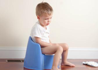 sad toddler boy wearing a white t-shirt sitting on a potty