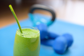 Green smoothie and dumbbells weights at the gym