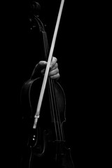 The hand holding the violin in dark colors on a black background