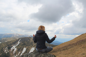 Blond hair woman having a meditation on the mountain peak