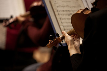 Fragment of a violin in the hands of a musician in a Symphony orchestra