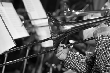 Hands of man playing the trombone in black and white