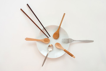 sharing concept - many wooden spoons, one silver spoon, chopsticks and a fork