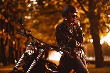 Motorcyclist with a cafe-racer motorcycle outdoors Wall mural