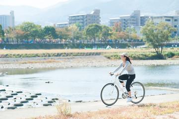 河川敷で自転車に乗っている日本人女性