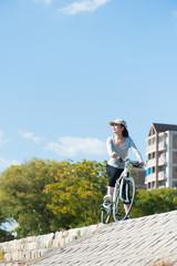 自転車に乗って遠くを見つめる女性