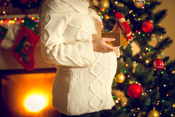 Toned shot of pregnant woman posing with Christmas gift box