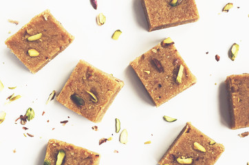 Homemade besan coconut burfi, traditional indian sweet made of coconut flakes, chickpea flour, cardamom and pistachio