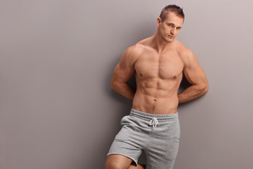 Handsome shirtless man leaning against a wall