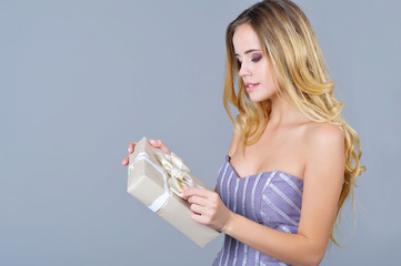 Portrait of an adorable woman in gala dress opening present box
