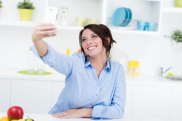 Moderne Hausfrau macht Selfie in der Küche