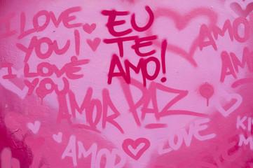 International love and peace graffiti in English and Brazilian Portuguese writing on pink wall in Rio de Janeiro, Brazil [English translation: I love you]