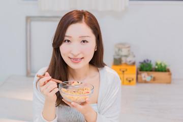 シリアルを食べるパジャマ姿の女性