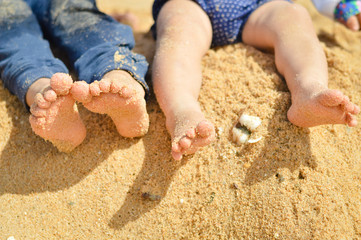 Closeup of two children's legs barefoot on summer sand seashore