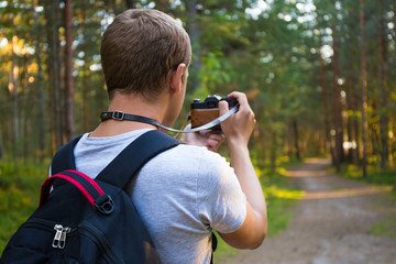 back view of man taking a photo with retro camera