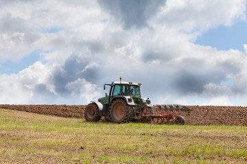 Farmer ploughing an overwintered field ready for planting the spring crop  against a dramatic cloudy sky using a tractor and plough