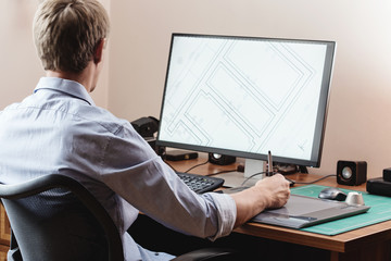 Graphic designer using digital tablet and computer in office or
