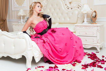 Blonde in long red dress is sitting on the bed with  roses