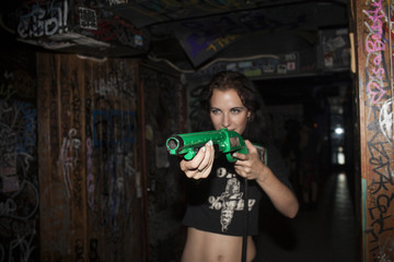 Young woman playing with plastic guns