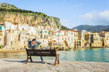 Young man sitting on bench, enjoying view of Cefalu coastline on Sicily island, Italy, Europe