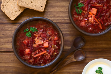 Vegetarian Borscht soup of Ukrainian origin made of beetroot, carrot, cabbage, potato, onion and celery in rustic bowls, photographed with natural light (Selective Focus, Focus on the soup)