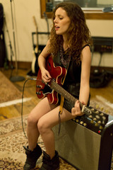 Young woman playing an electric guitar