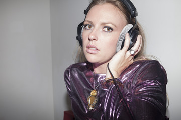 Young woman listening to music through large headphones