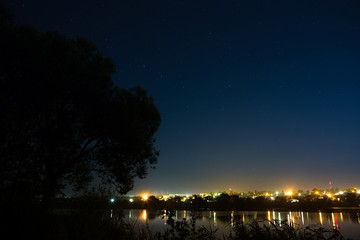 Stars in the night sky on a background city lighting. The bright