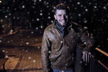 young man smiling during a snowy night