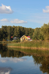 bright yellow house on lake autumn