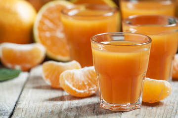 Fresh tangerine juice with slices of mandarin on old wooden back