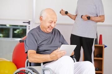 Behinderter Mann im Rollstuhl mit Tablet PC