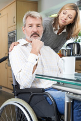 Woman Comforting Depressed Man In Wheelchair At Home