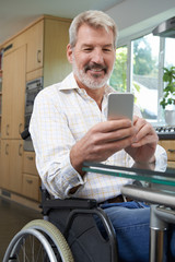 Disabled Man In Wheelchair Texting On Mobile Phone At Home