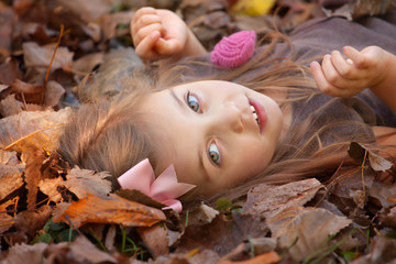 beautiful little girl with brown hair laying on the ground