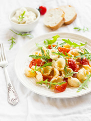 Orecchiette pasta with cherry tomatoes, arugula and Parmesan for a bright plate on a white surface
