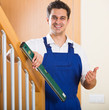 Builder examines stairs railing with spirit level